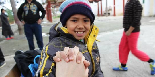 Un niño refugiado sonriente agarra la mano del fotógrafo