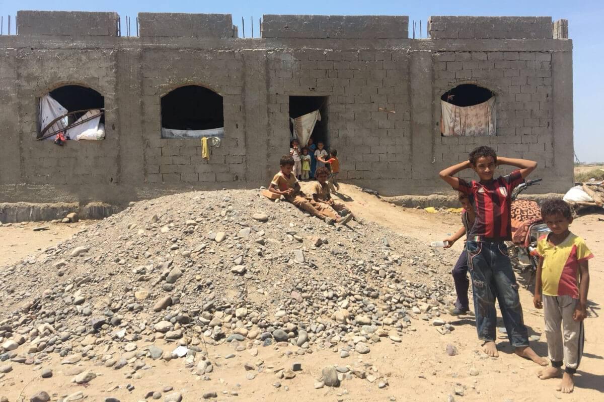 Niños yemeníes junto a una construcción a medio terminar
