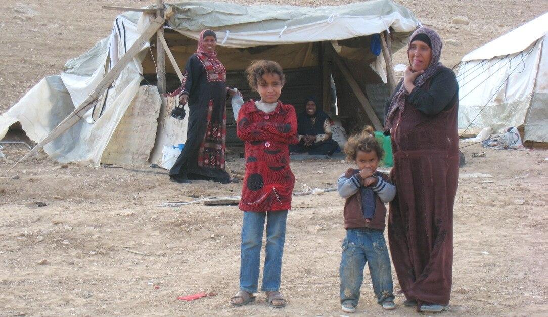 Varias mujeres y niñas posando delante su tienda de campaña
