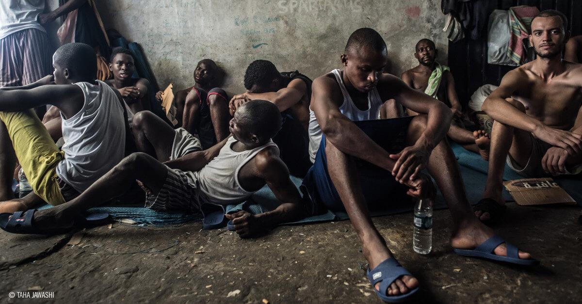 Varios hombres refugiados sentados en el suelo