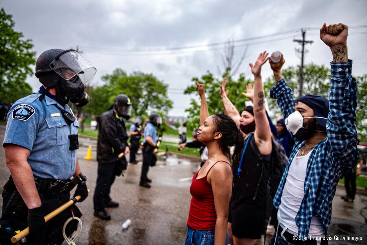 Manifestantes frente a la policia protestando por la muerte de George Floyd