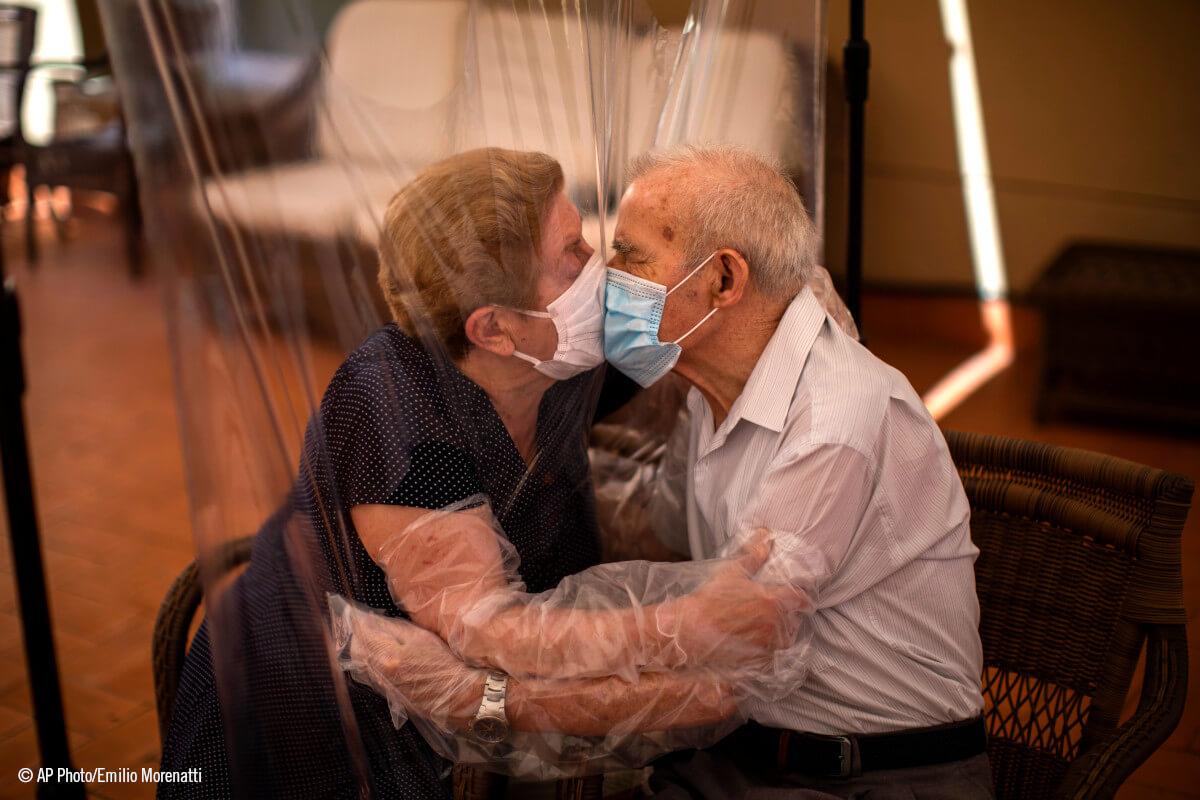 Una pareja de amyores se besa a través de una lámina de plastico