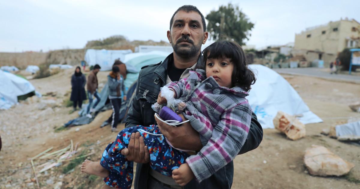 Un refugiado llevando a su hija en brazos