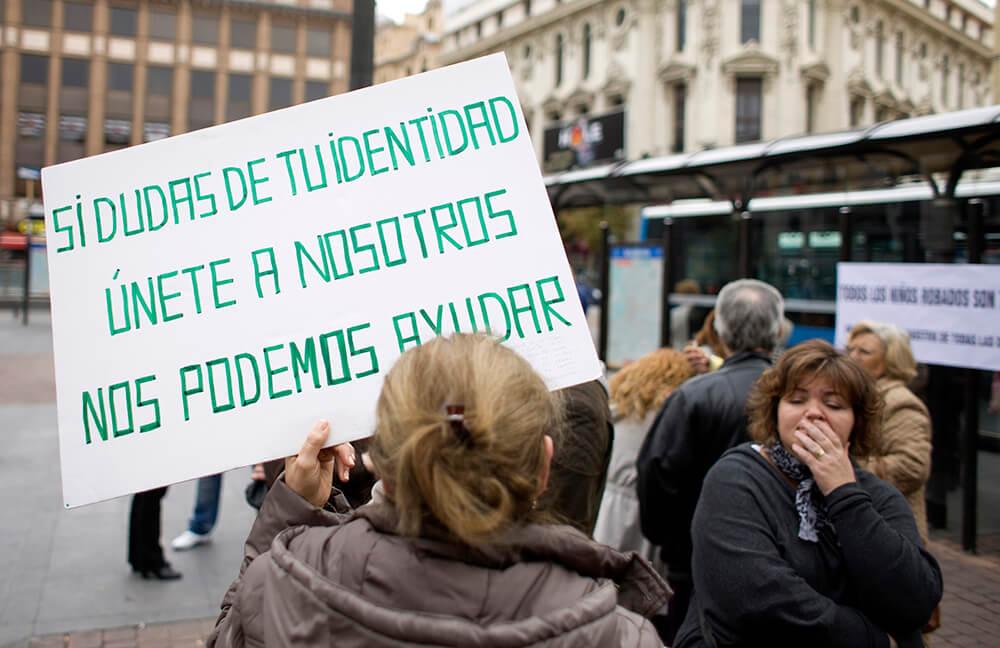 Una mujer sostiene una pancarta contra el posible robo de bebés robados.
