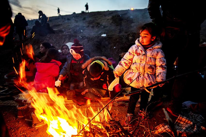 Personas refugiadas y migrantes se calientan junto al fuego mientras intentan entrar en Grecia desde Turquía, 1 de marzo de 2020 en Edirne, Turquía