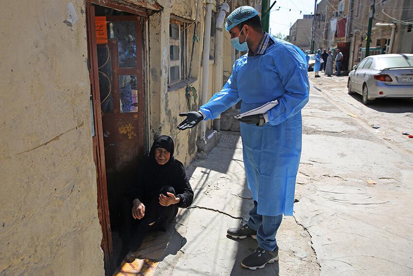 Un médico especializado en un hospital público iraquí habla con una anciana antes de hacerle la prueba de COVID-19 en el suburbio de Ciudad Sadr en la capital Bagdad el 2 de abril de 2020