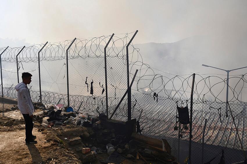 Un migrante mira a través de una alambrada semiderruida