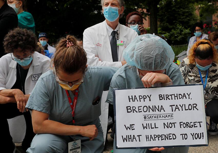 Las enfermeras Chelsea Smith y Elizabeth Stocksdale se arrodillan durante los 8 minutos y 46 segundos de silencio durante una vigilia en el Hospital Brigham and Women's, donde muchos pacientes con enfermedad por coronavirus (COVID-19) han sido tratados, contra la muerte en custodia policial de George Floyd en Minneapolis, en Boston