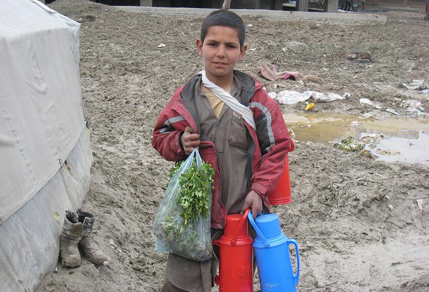 Un chico de 14 años, que vive en el asentamiento de desplazados internos de Chaman-e- Babrak, compra verduras en el mercado local, donde vende té para ganarse la vida.