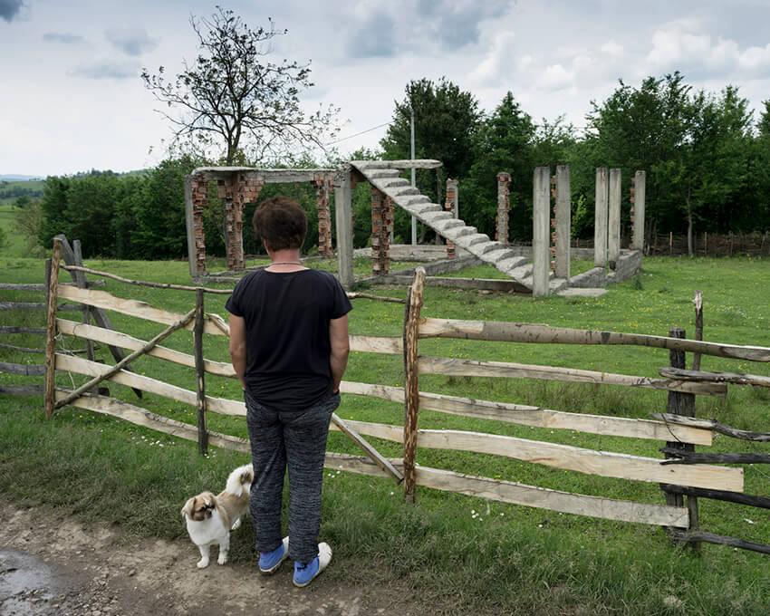 Una sobreviviente mirando una casa familiar destruida en el este de Bosnia. La asistencia estatal y los programas de ayuda a menudo no llegan a las mujeres en áreas remotas.