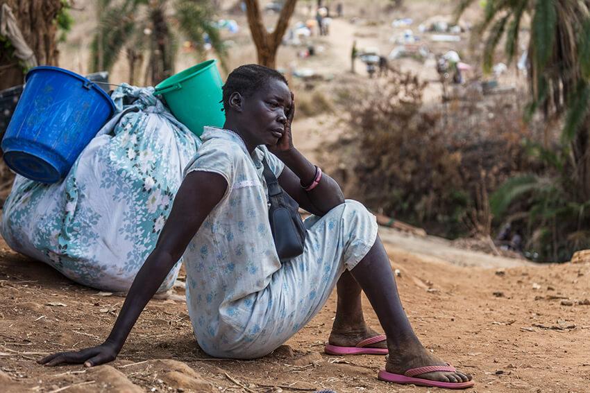Una mujer descansa junto a su equipaje antes de cruzar el arroyo Kaya cerca de la ciudad de Afoji, distrito de Moyo, en el norte de Uganda.