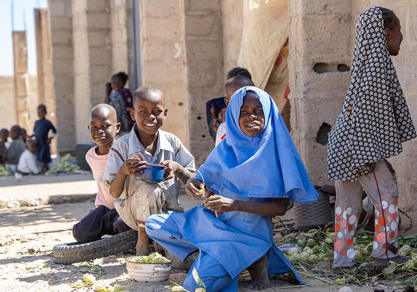 Después de terminar la clase de primaria, una niña (con uniforme azul) juega con otros niños que no están en la escuela, antes de volver a casa en Kaleri, Estado de Borno, Nigeria, 2019.