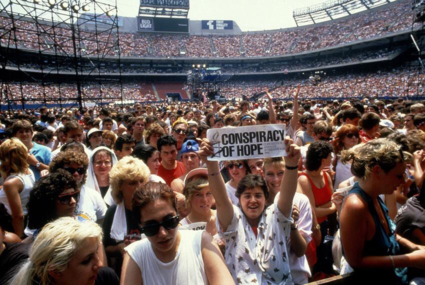 Aficionados y aficionadas asisten a un concierto organizado por Amnistía Internacional en el Giants Stadium, Nueva Jersey.