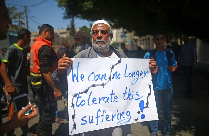 Un palestino cuya casa fue destruida por Israel sostiene una pancarta durante una protesta frente a la sede del Programa de las Naciones Unidas para el Desarrollo (PNUD), en la ciudad de Gaza el 20 de abril de 2016.