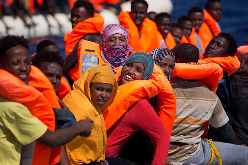 Varias mujeres migrantes sonríen a bordo de un bote mientras navegan en el mar Mediterráneo hacia las costas italianas