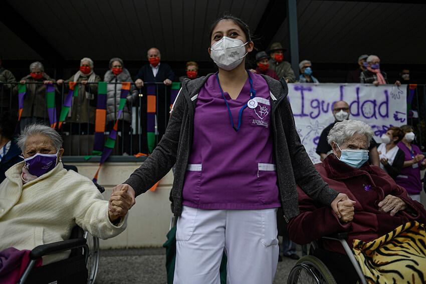Una trabajadora sanitaria de una residencia de ancianos da la mano a dos personas mayores.