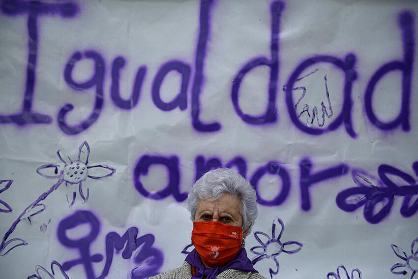 """Una residente de la residencia de ancianos San Jerónimo posa frente a una pancarta que recoge la palabra """"Igualdad""""."""
