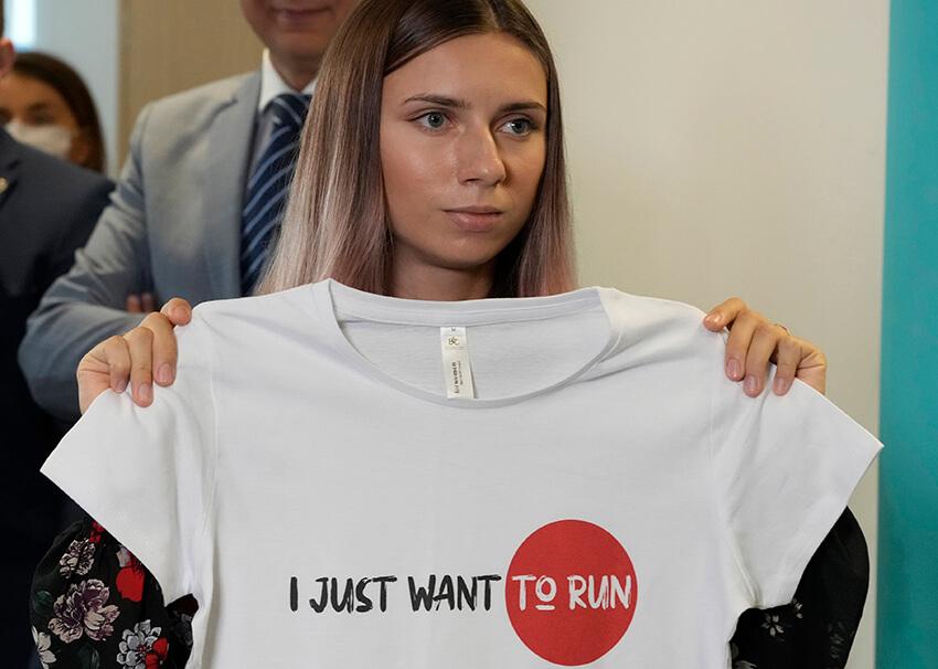 """La velocista olímpica bielorrusa Krystsina Tsimanouskaya sostiene una camiseta con el lema """"Sólo quiero correr"""", el 5 de agosto de 2021."""