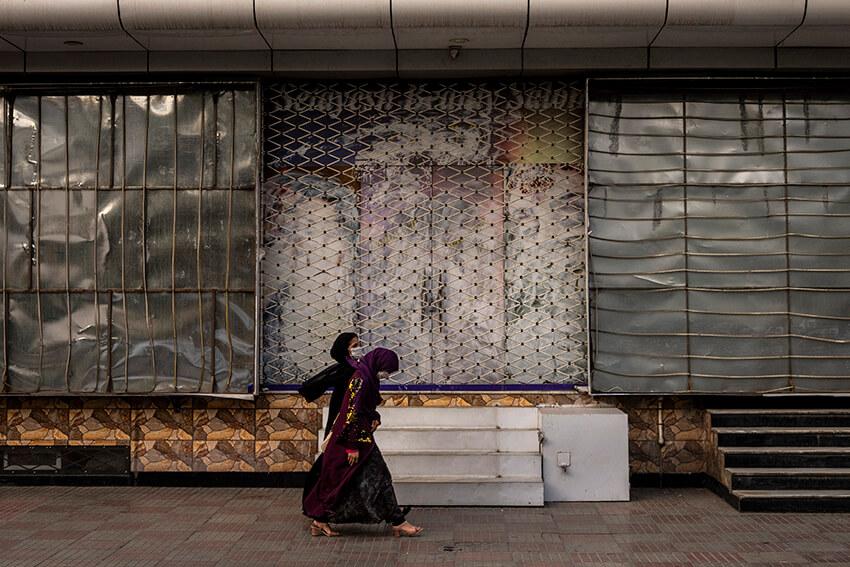 Unas mujeres afganas pasan por delante de un salón de belleza cerrado en Kabul, Afganistán, el 11 de septiembre de 2021. Desde que los talibanes se hicieron con el control de Kabul, se han eliminado o tapado varias imágenes en las que aparecen mujeres en el exterior de los salones de belleza.