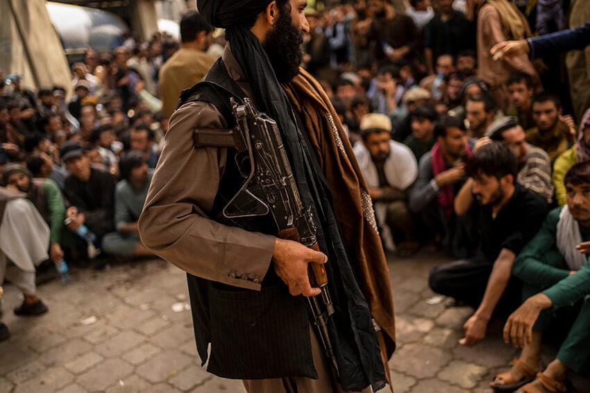Un combatiente talibán controla a una multitud que espera para retirar dinero de una sucursal bancaria en Kabul, Afganistán, el 12 de septiembre de 2021.