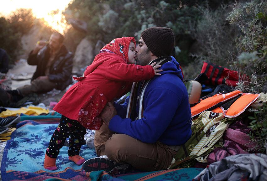 Un padre y una hija se dan un beso mientras esperan a viajar en un bote hasta las islas griegas desde Turquía