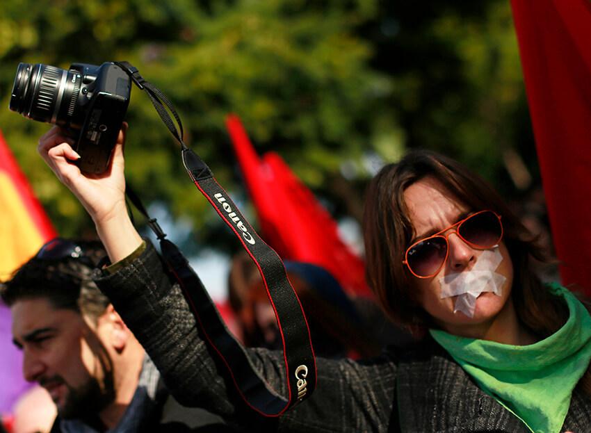 Un manifestante sostiene una cámara de fotos mientras participa en una protesta contra la nueva ley de seguridad ciudadana en Sevilla, el 27 de diciembre de 2014.