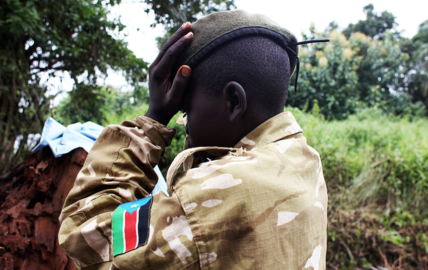 Un ex niño soldado arregla su boina mientras asiste a una ceremonia de liberación de niños y niñas soldados, en las afueras de Yambio, Sudán del Sur, el 7 de agosto de 2018.