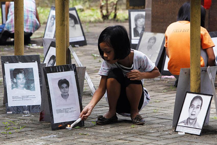 Una niña enciende una vela cerca de una serie de fotos de personas desaparecidas en un santuario conmemorativo levantado por la organización no gubernamental Familias de Víctimas de Desapariciones Involuntarias (FIND), en Manila.