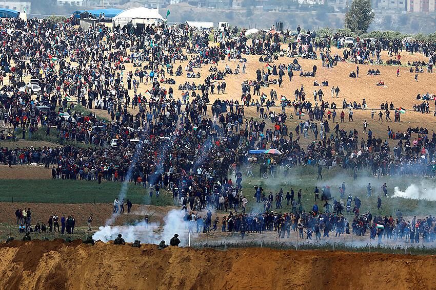 Soldados israelíes disparan gas lacrimógeno desde el lado israelí de la frontera entre Israel y Gaza, mientras los palestinos protestan desde la frontera de Gaza, el 30 de marzo de 2018. © REUTERS/Amir Cohen
