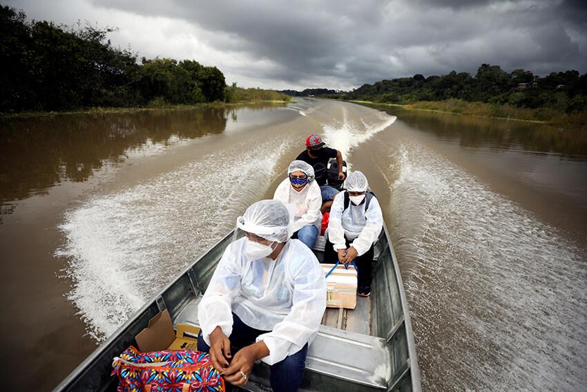 Profesionales de la salud viajan en un bote a orillas del río Solimoes para administrar la vacuna AstraZeneca a los residentes en Manacapuru, estado de Amazonas, Brasil, febrero de 2021.