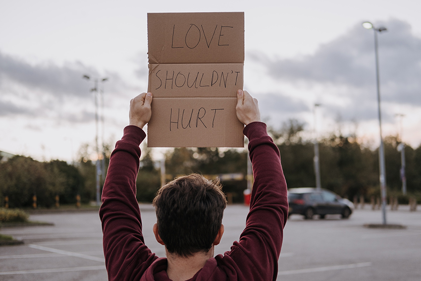 """Chico que sostiene un cartel que dice """"el amor no duele"""""""