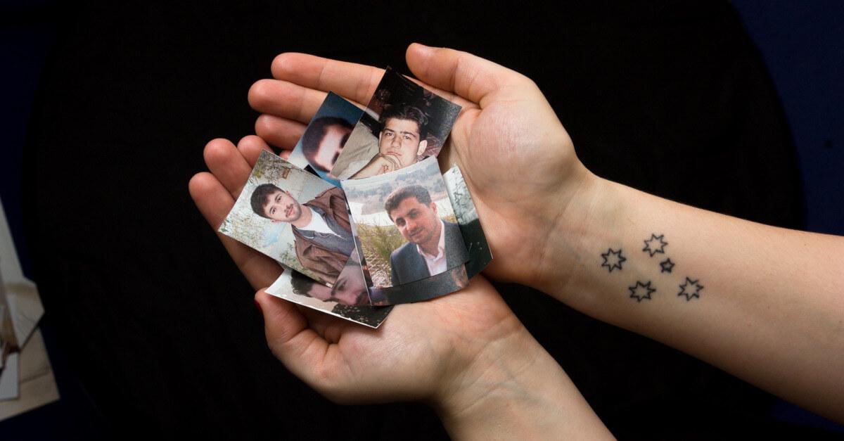 Unas manos con fotos de personas desaparecidas